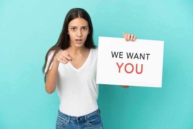 Giovane donna francese isolata su sfondo blu, tenendo la scheda we want you e indicando la parte anteriore
