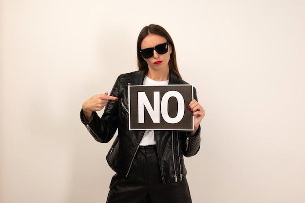 Giovane donna francese isolata su sfondo bianco in possesso di un cartello con testo no