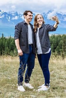 Giovane coppia amichevole di turisti uomo e donna scattare una foto al telefono in montagna in vacanza durante un viaggio
