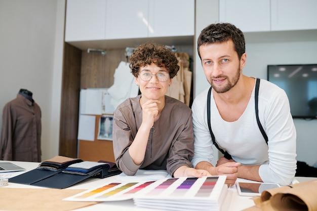 Giovani stilisti amichevoli che ti guardano mentre si chinano sulla scrivania e scelgono campioni di tessuto