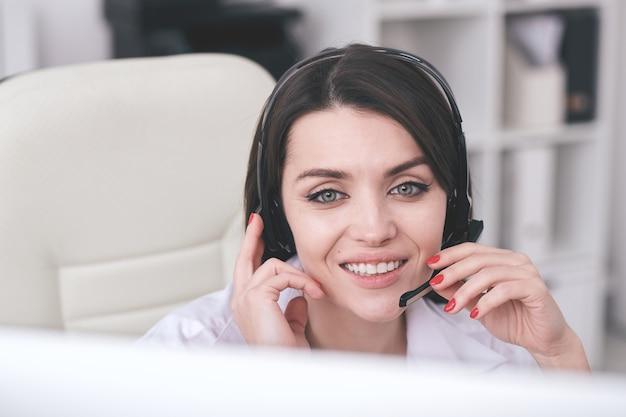 Operatore telefonico amichevole giovane con sorriso a trentadue denti seduto davanti al monitor del computer e rispondendo alle domande dei clienti online