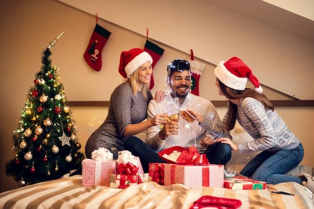 I giovani amici festeggiano il natale con bevande e regali seduti sul letto