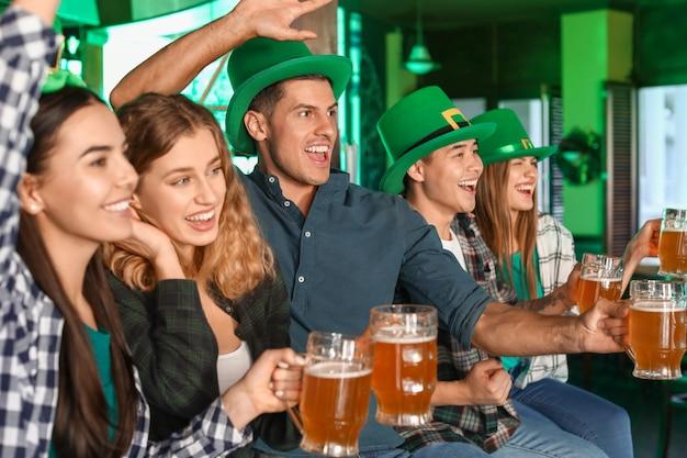 Giovani amici che celebrano il giorno di san patrizio nel pub