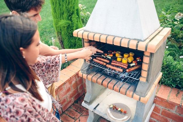 Giovani amici che cucinano mais, salsicce e spiedini di verdure in un barbecue durante la festa estiva