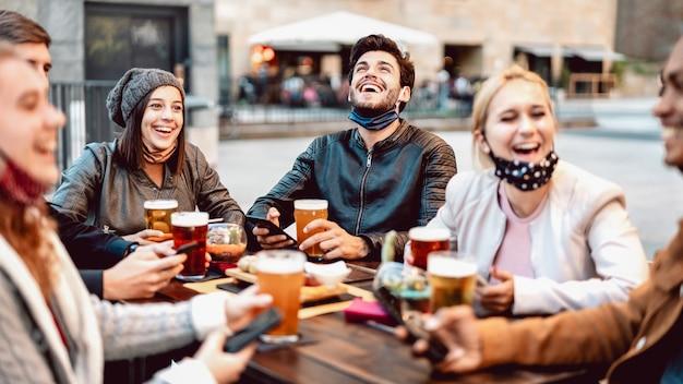 Giovani amici che bevono birra che indossa la maschera per il viso