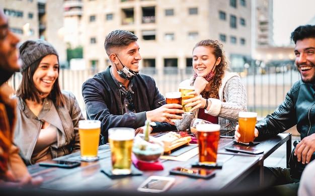 Giovani amici che bevono birra con maschera facciale aperta