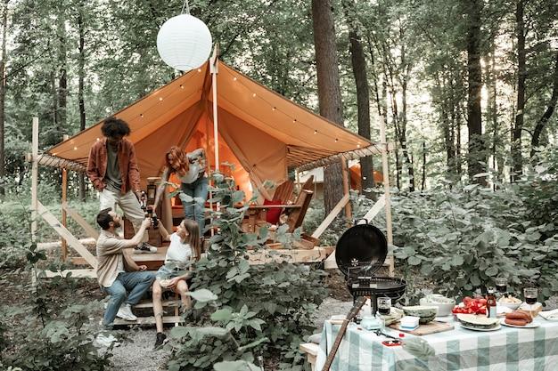 I giovani amici si godono la serata soleggiata nel glamping della foresta. la gente ride brindando tintinnando bottiglie di sidro di birra e bicchieri di vino vicino al falò vicino alla tenda. campeggio uscire insieme, ritrovo sociale all'aperto