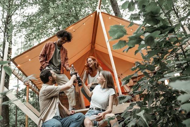 I giovani amici si godono la serata soleggiata nel glamping della foresta. la gente ride e brinda con bottiglie di sidro di birra e bicchieri di vino vicino al falò vicino alla tenda. campeggio uscire insieme, ritrovo sociale all'aperto