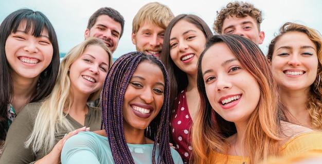 Giovani amici di diverse culture e razze che scattano foto facendo facce felici - gioventù, generazione millenaria e concetto di amicizia con gli studenti che si divertono insieme - focus su ragazze in primo piano