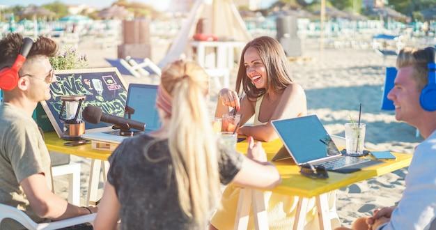 Giovani amici che si divertono a fare un'intervista in streaming live a un influencer al bar della spiaggia