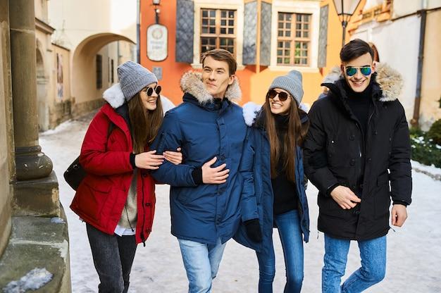 Giovani amici divertendosi all'aperto nell'orario invernale. concetto di amicizia e divertimento con le nuove tendenze in w