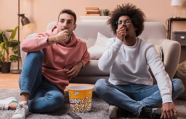 Giovani amici a casa che mangiano popcorn