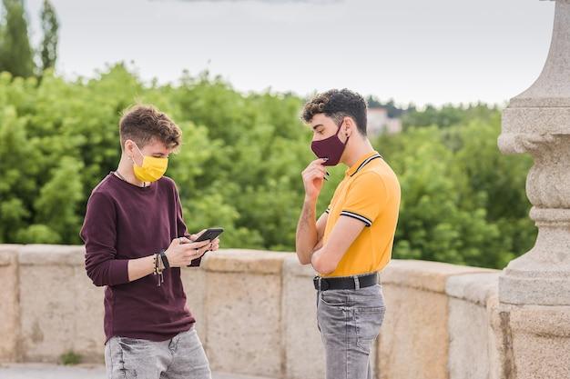 Giovani amici che si incontrano con la comunicazione della tecnologia smartphone per il distanziamento sociale
