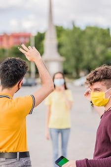 Giovani amici che si incontrano con il distanziamento sociale per il chroma key dello smartphone coronavirus