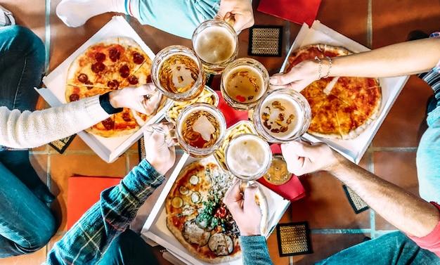 Giovani amici coinquilini che mangiano pizza da asporto a casa dopo il college