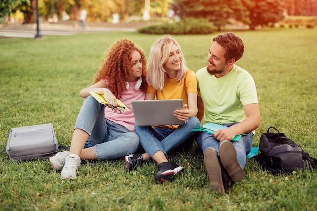 Giovani amici seduti sull'erba e utilizzando laptop per i compiti
