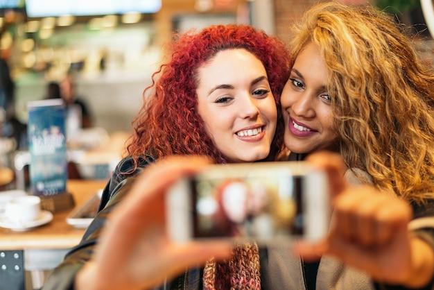 Giovani amici che si fanno un selfie con il cellulare in un bar ristorante