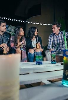 Giovani amici che parlano e bevono in una festa all'aperto. concetto di amicizia e celebrazioni.