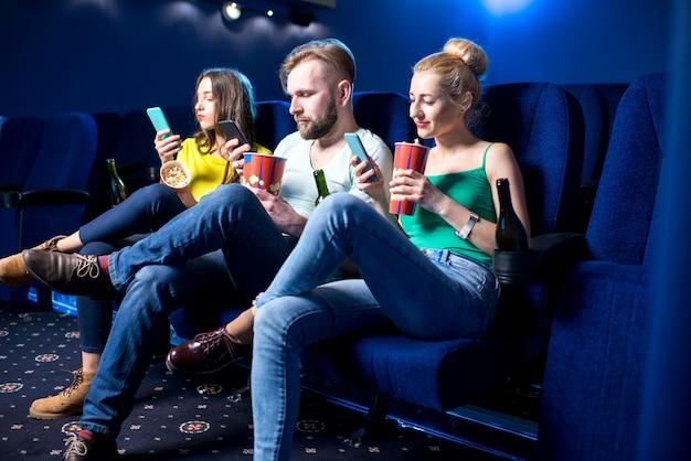 Giovani amici che usano smartphone seduti insieme al cinema