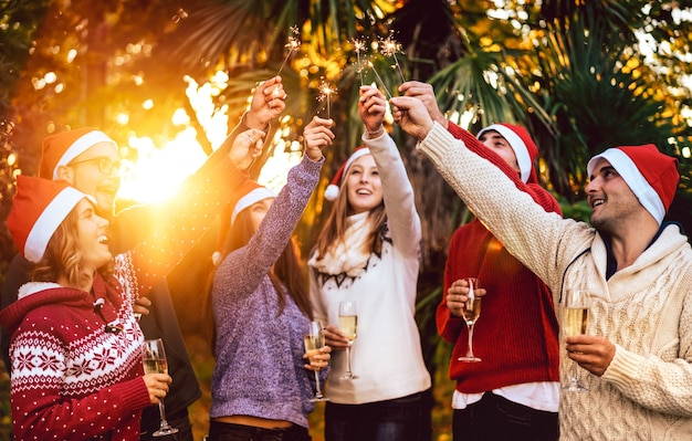 Giovani amici con cappelli di babbo natale che festeggiano il natale con un brindisi con champagne e vino all'aperto
