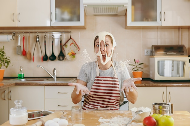 La giovane simpatica donna allegra e sorridente mette su un impasto con i buchi sul viso e si diverte in cucina. cucinare a casa. prepara da mangiare.