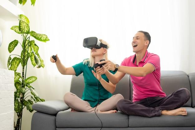 Giovane coppia divertente che gioca ai videogiochi occhiali per realtà virtuale nel loro appartamento - persone felici che si divertono con le nuove tendenze tecnologiche - concetto di gioco - focus on woman joypad