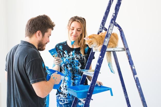 Giovane coppia divertente con il gatto facendo lavori di ristrutturazione nel nuovo appartamento.