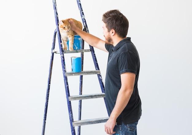 Giovane uomo divertente e un gatto durante la ristrutturazione in appartamento.