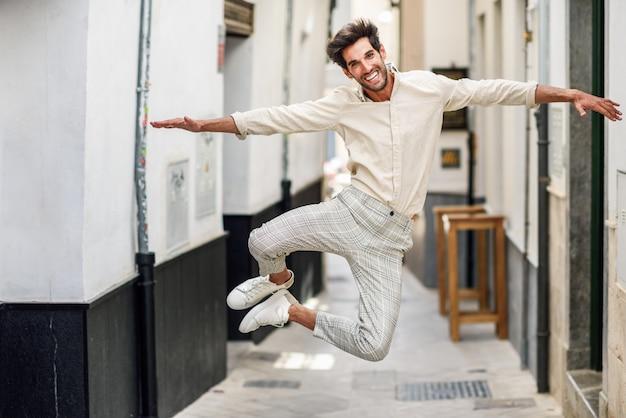 Giovane uomo divertente che salta in strada