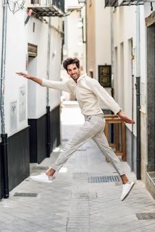 Giovane uomo divertente che salta in strada.