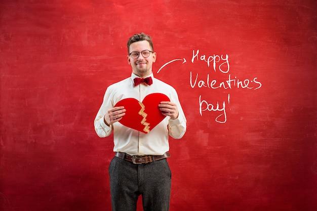 Il giovane uomo divertente con cuore spezzato e incollato astratto su sfondo rosso studio. concetto - amore infelice e felice. il concetto di buon san valentino