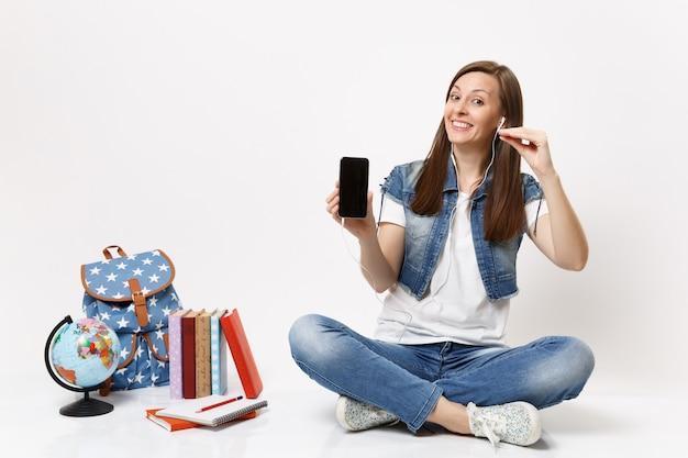 La giovane studentessa graziosa divertente con il telefono cellulare degli auricolari con lo schermo vuoto nero in bianco ascolta la musica vicino al globo, libri dello zaino isolati sul muro bianco