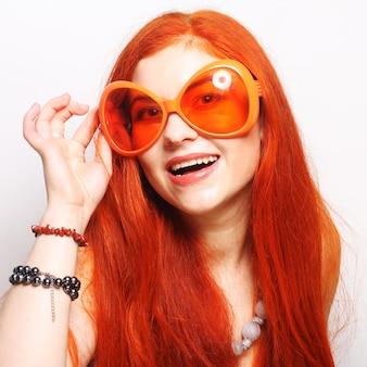 Giovane donna dai capelli rossi divertente con grandi occhiali arancioni