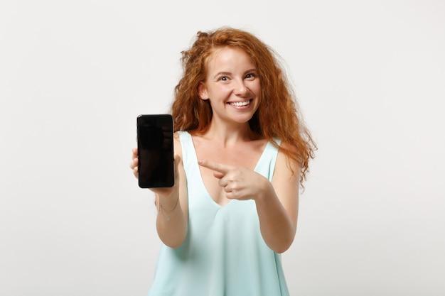 Giovane ragazza divertente della donna della testarossa nella posa leggera dei vestiti casuali isolata su fondo bianco. concetto di stile di vita della gente. mock up copia spazio. puntare il dito indice sul telefono cellulare con schermo vuoto vuoto.