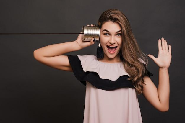 Giovane donna divertente che ascolta attraverso un barattolo di latta