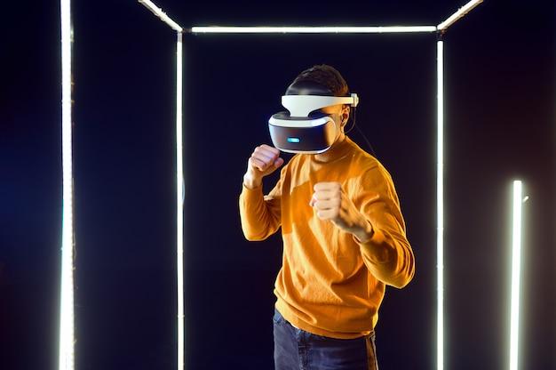 Giovane giocatore che combatte in cuffia per realtà virtuale e gamepad in cubo luminoso, vista frontale. interno del club di gioco scuro, riflettori sullo sfondo, tecnologia vr con visione 3d