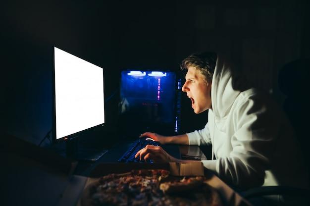 Il giovane giocatore in una felpa con cappuccio gioca di notte su un computer, guarda lo schermo con facce sorprese e grida
