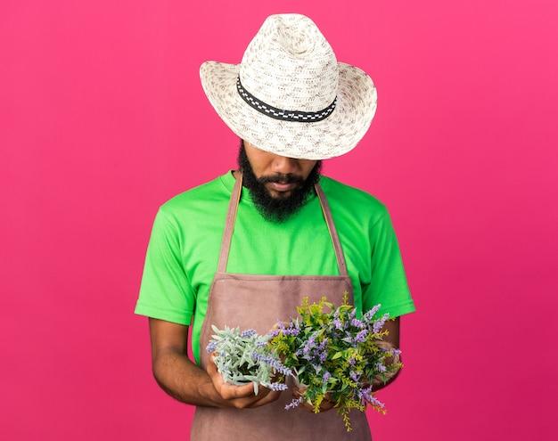 Giovane giardiniere afro-americano che indossa un cappello da giardinaggio che tiene e guarda i fiori in un vaso di fiori
