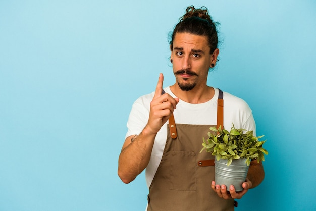 Uomo caucasico del giovane giardiniere che tiene una pianta isolata su fondo blu che mostra il numero uno con il dito.
