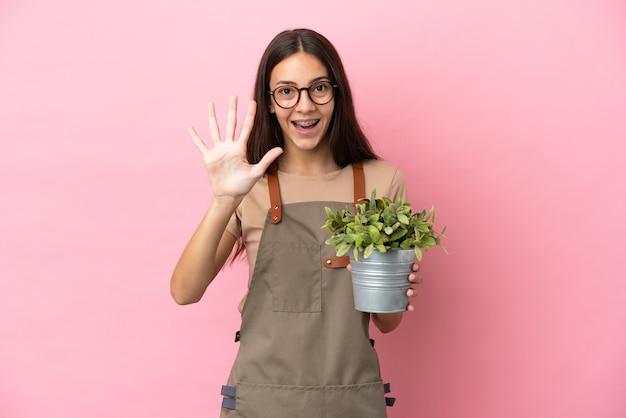 Ragazza giovane giardiniere che tiene una pianta isolata su sfondo rosa contando cinque con le dita