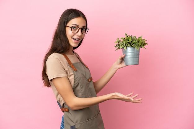 Ragazza giovane giardiniere che tiene una pianta isolata su sfondo rosa che estende le mani di lato per invitare a venire