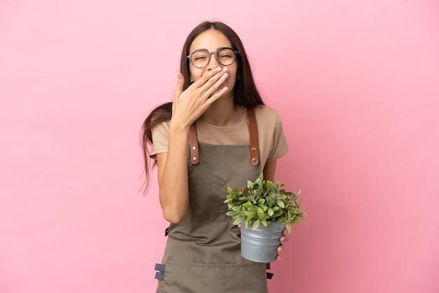 Ragazza giovane giardiniere che tiene una pianta isolata su sfondo rosa felice e sorridente che copre la bocca con la mano