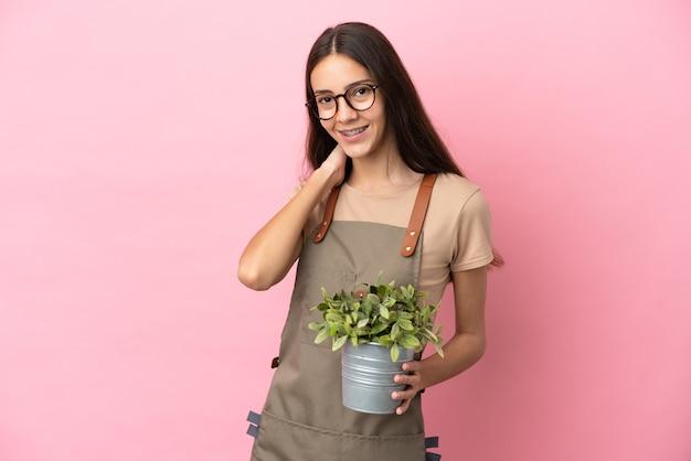 Ragazza giovane giardiniere che tiene una pianta isolata su sfondo rosa ridendo