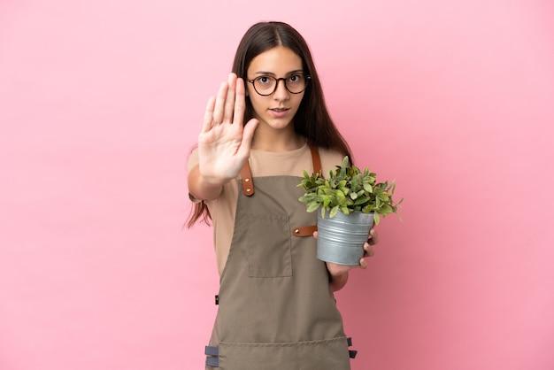 Giovane ragazza del giardiniere che tiene una pianta isolata su fondo rosa che fa gesto di arresto stop