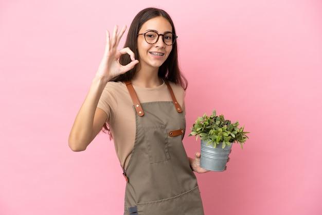 Giovane ragazza del giardiniere che tiene una pianta isolata su fondo rosa che mostra il segno giusto con le dita