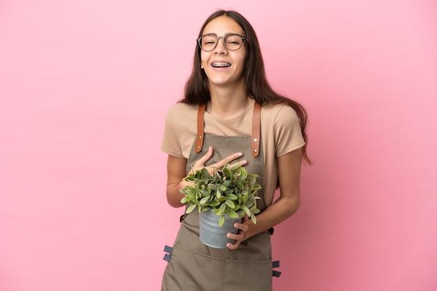 Giovane ragazza del giardiniere che tiene una pianta isolata su fondo rosa che sorride molto