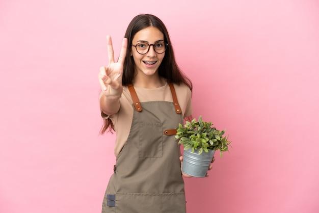 Giovane ragazza del giardiniere che tiene una pianta isolata su fondo rosa che sorride e che mostra il segno di vittoria