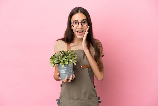 Ragazza giovane giardiniere che tiene una pianta isolata su sfondo rosa con espressione facciale sorpresa e scioccata