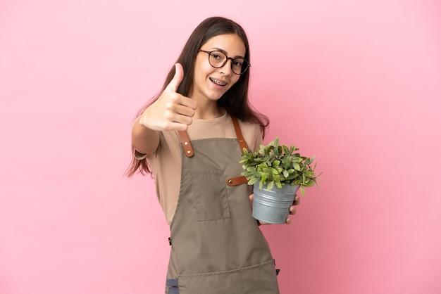 Giovane ragazza giardiniere che tiene una pianta isolata su sfondo rosa con il pollice in alto perché è successo qualcosa di buono