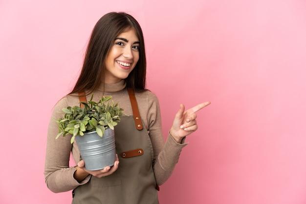 Giovane ragazza del giardiniere che tiene una pianta isolata sulla parete rosa che indica indietro